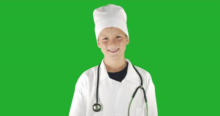 sebész : Portrait of doctor boy, smiling . Green screen hromakey background for keying.