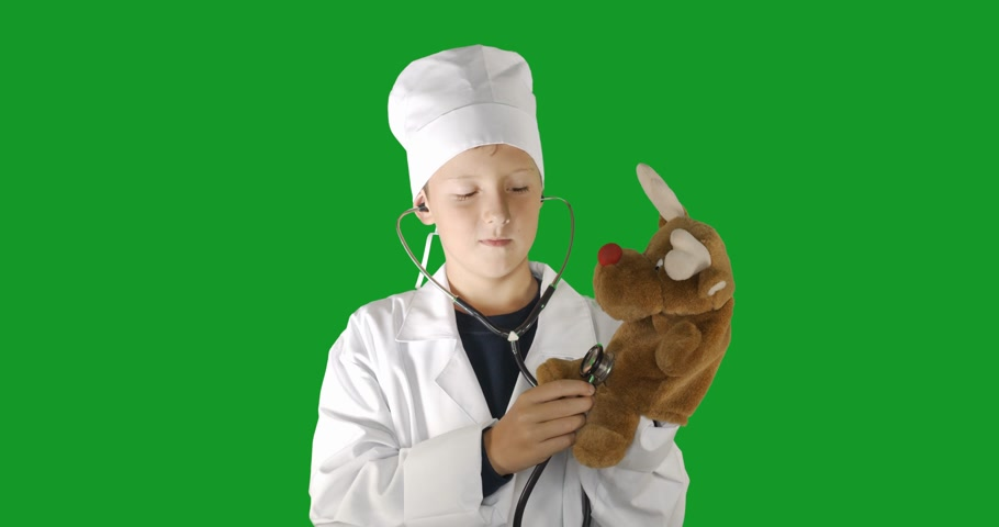 hromakey : Portrait of doctor boy, who treats a toy . Green screen hromakey background for keying.