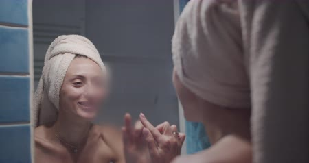 úmido : The Young adult woman wipe mirror glass in foggy bathroom. The Girl stay wrapped into white towel and smiling on the mirorr.