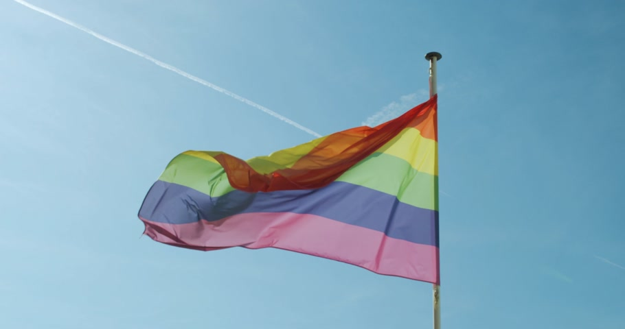 seksualiteit : Big Rainbow flag gay pride LGBTQ developing by the wind against the blue sky.