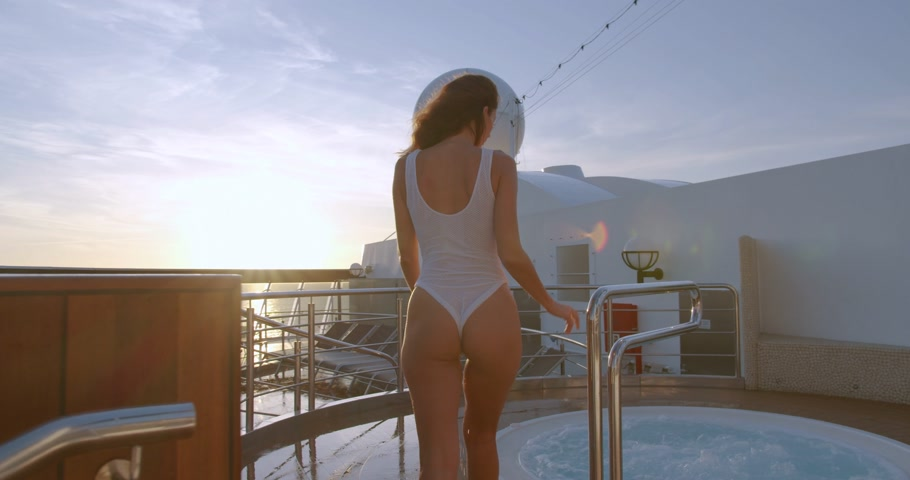vasca bagno : Woman Going In Hot Tub Spa At With Amazing Sunrise sea View.