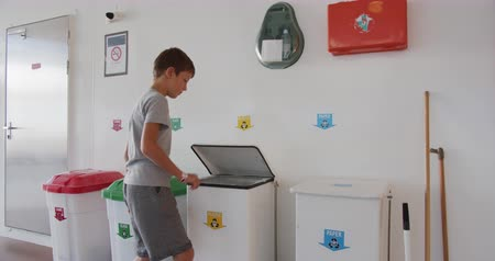 catastrophe ecologique : Boy throws waste in colorful, plastic garbage bins. Waste sorting and recycling, saving the environment. Sorting of household waste, composting, zero waste. Sorting garbage. Vidéos Libres De Droits