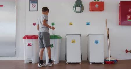 litter box : Boy throws a plastic bottle into the right trash can. Recycling plastic, proper sorting of garbage. Stock Footage
