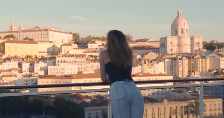 europa : Happy woman standing on the balcony with view on the city Lisbon, Portugal.