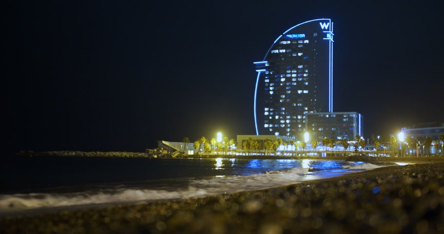 Barcelona, Spain - October 15, 2019: Barcelona, Spain. View of the hotel-sail on the beach of Barceloneta in night. Stok Video