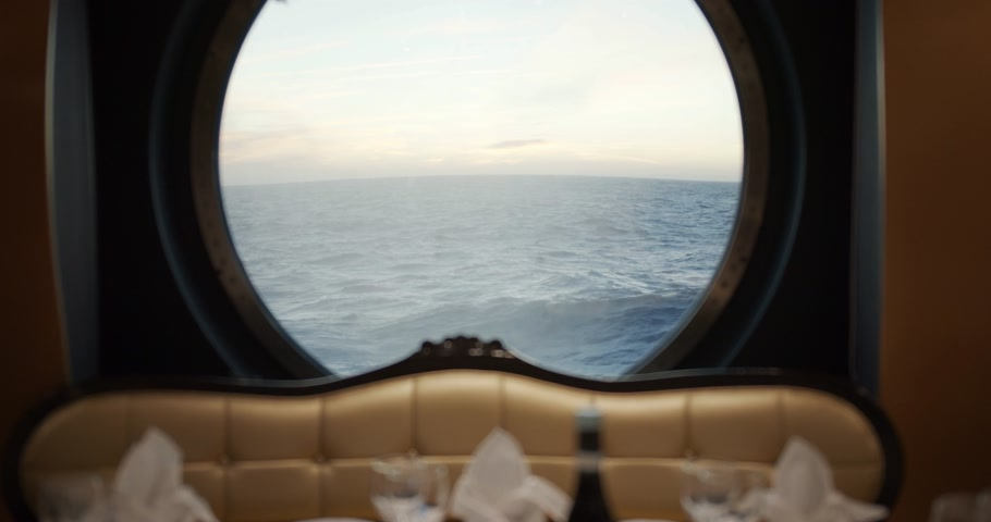 személyszállító hajó : View through a porthole on a stormy sea with waves on cruise ship in restorante. Stock mozgókép