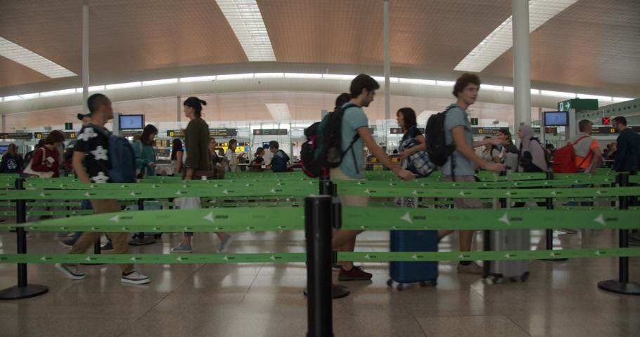 crowded : Barcelona, Spain - October 20, 2019: A huge queue inside the airport. Passengers goin line for checking passports. Timelapse.