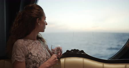 személyszállító hajó : Woman Watching Sunset From window On Luxury Cruise Ship with a glass of wine.