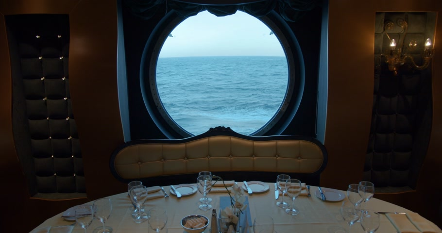 servido : A served table in a restaurant against the backdrop of a huge round window on a cruise ship.