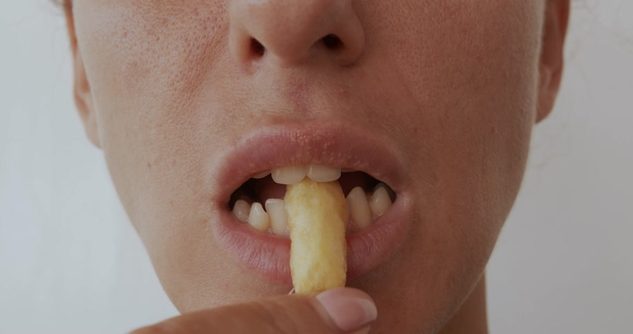 жирный : Woman eating French fries, harmful and tasty fast food, close up.