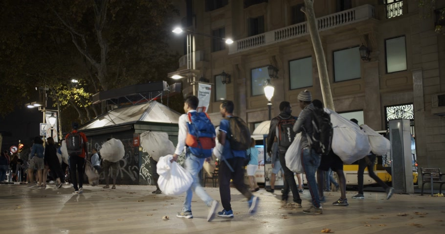 migrants : Barcelona, Spain - October 20, 2019: Police dispersal of black migrants, street vendors on the streets of Barcelona at night. The Problem of Illegal Immigration in Europe. Timelapse.