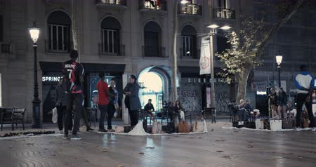 göçmen : Barcelona, Spain - October 20, 2019: Black migrants, street vendors on the streets of Barcelona at night. The Problem of Illegal Immigration in Europe. Timelapse.
