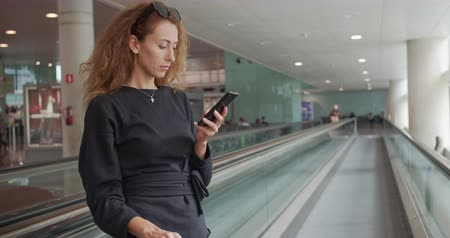 escalier mécanique : Young girl using smartphone in airport. Happy European woman with with luggage uses mobile in terminal.