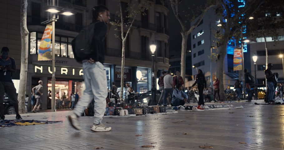 migrants : Barcelona, Spain - October 20, 2019: Street vendors on the streets of Barcelona at night. Stock Footage