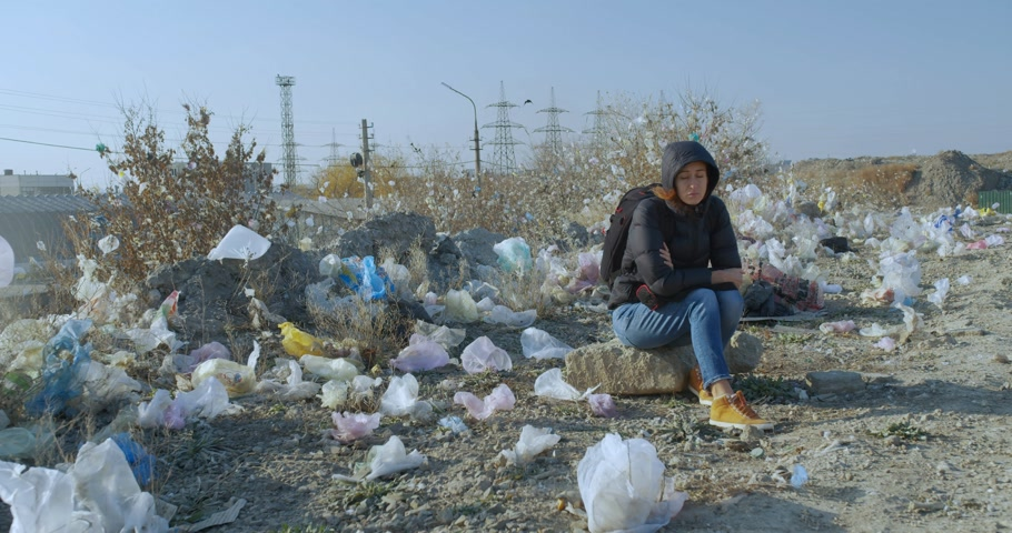 coletando : A girl sits in a place contaminated with plastic bags. The scale of the planet s pollution is impressive. Stock Footage