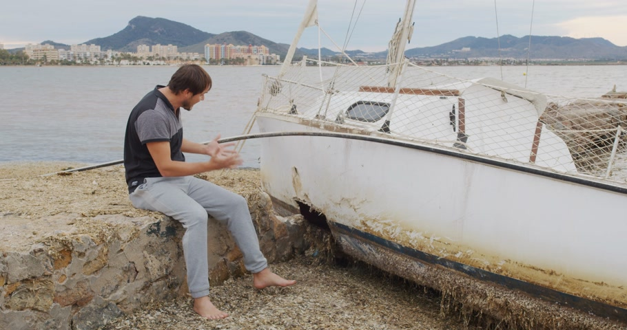mastro : The man sits in despair near his yacht broken after a storm.