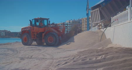 buldozer : Torrevieja, Spain - December 21, 2019: Truck and tractors work on sea. Construction site at summer day, expansion and improvement of the beach.