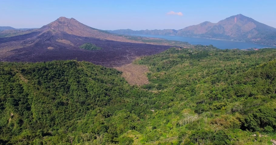 Aerial footage of gunung Batur volcano. Drone view of road and volcano.