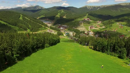 Aerial flight ski slope in summer. Drone flying over mountain forests and village