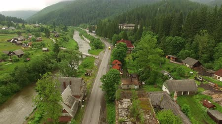Aerial footage along the river road in the mountain village and forest