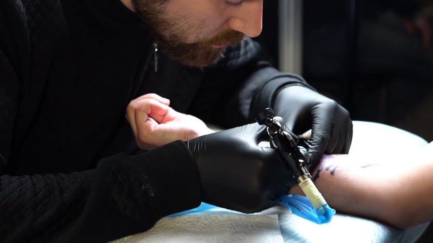 Close-up of a tattooist with tattoo machine. Shooting in slow motion Stock Footage