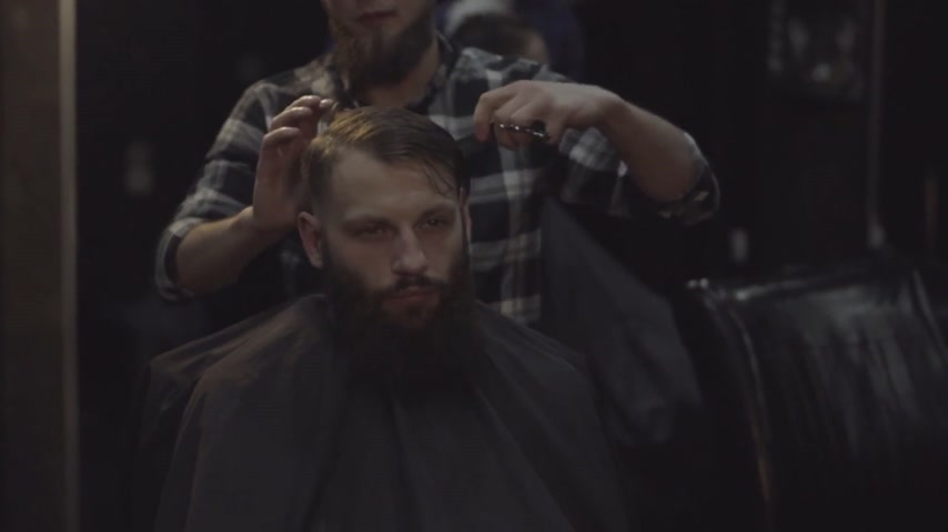 Barber combing the hair of the male bearded client at a barber shop