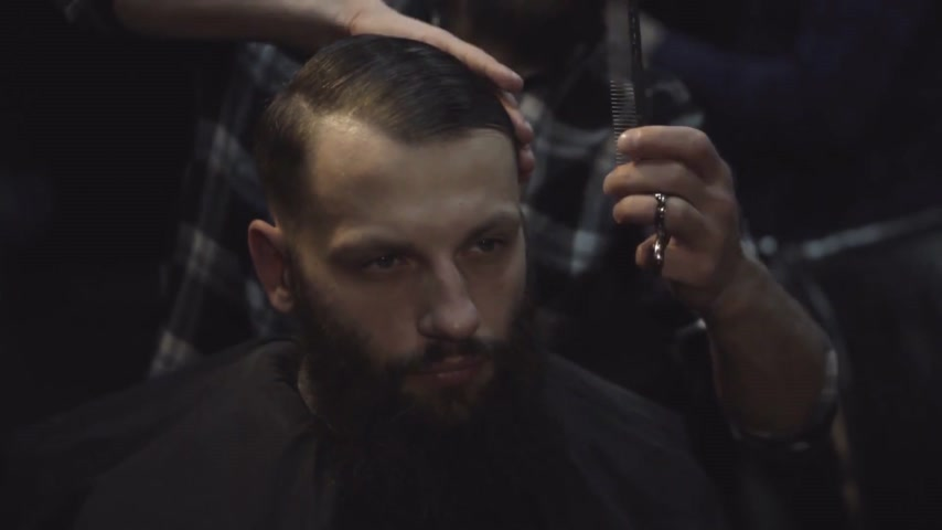 Male barber combing hair of a male client at barbershop