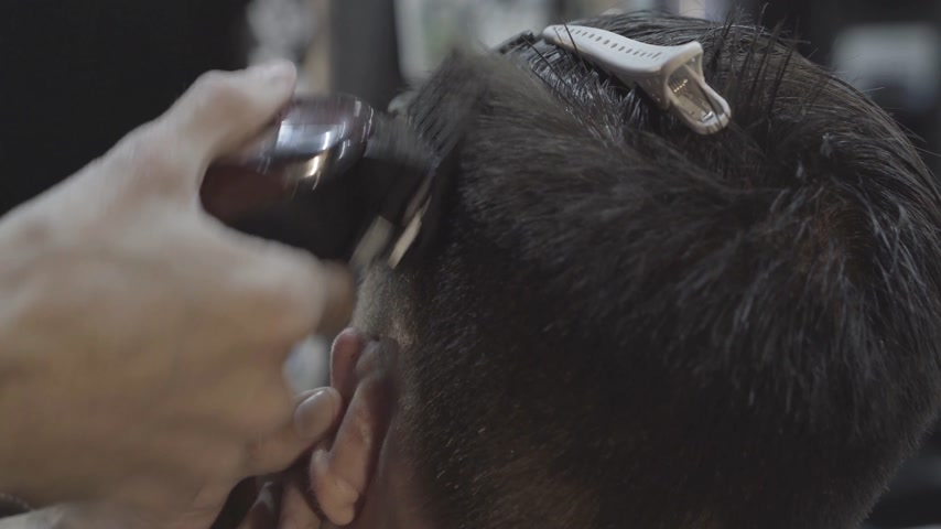 Barber cuts the hair of the client with machine for haircuts. Haircut men Barbershop