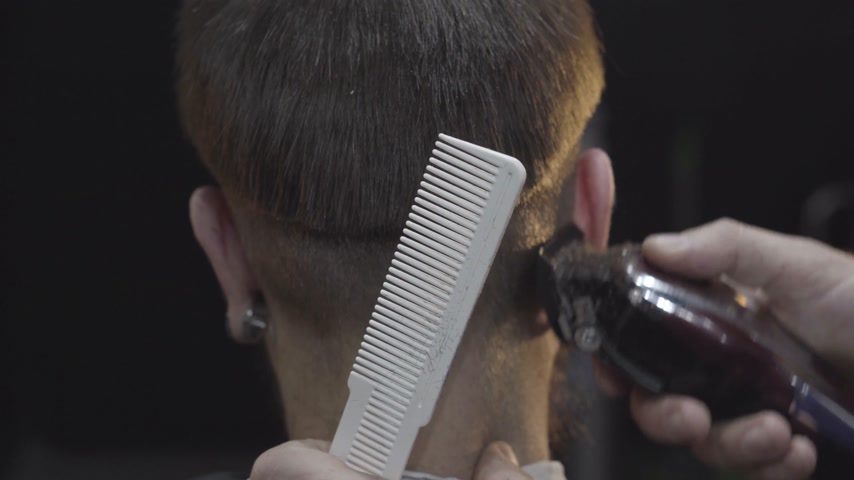 Master in stylish mens barbershop cuts the hair of the client with trimmer Stock Footage