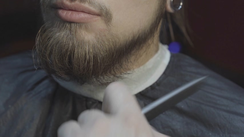 Close-up of a barber cuts beard a of a young bearded man
