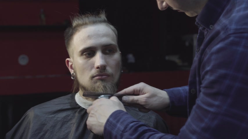 Barber cuts beard using trimmer at a barber shop