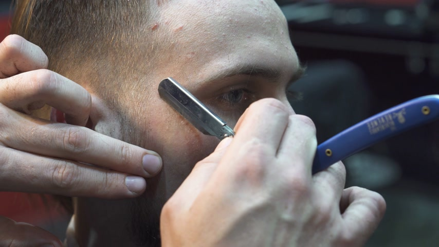 Close-up of Barber shaves client's beard with a straight razor blade in a barbershop