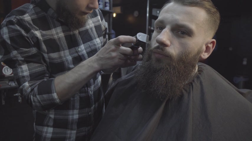 Barber cutting beard of young bearded man with electric razor at a barber shop