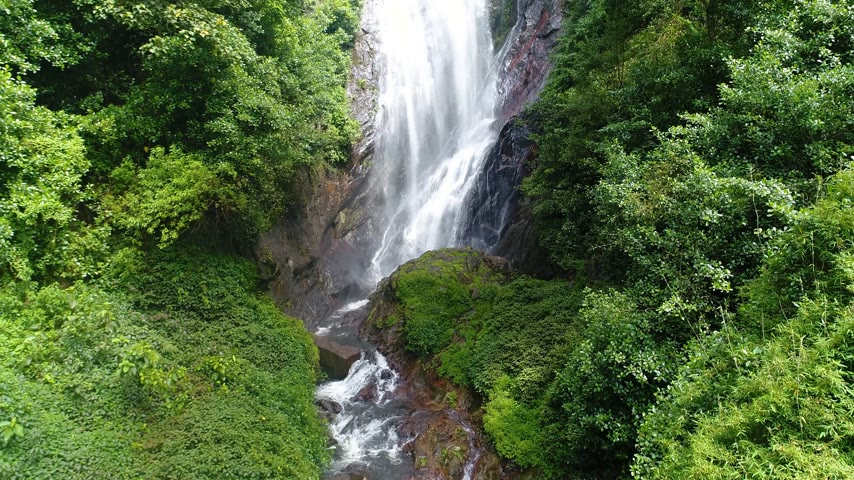 Aerial view from the bottom up of the waterfall flows down the slope on Adams Peak in Sri Lanka Stock Footage