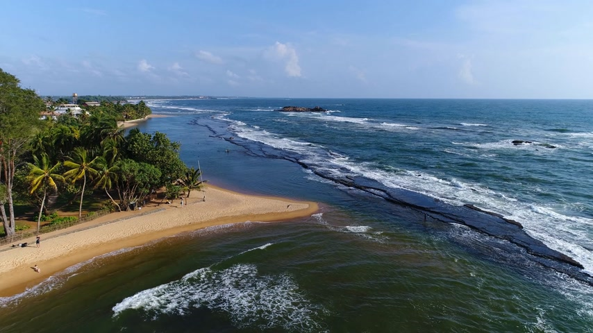 Aerival view in motion sea sandy beach and light waves at the resort in Sri Lanka Stock Footage