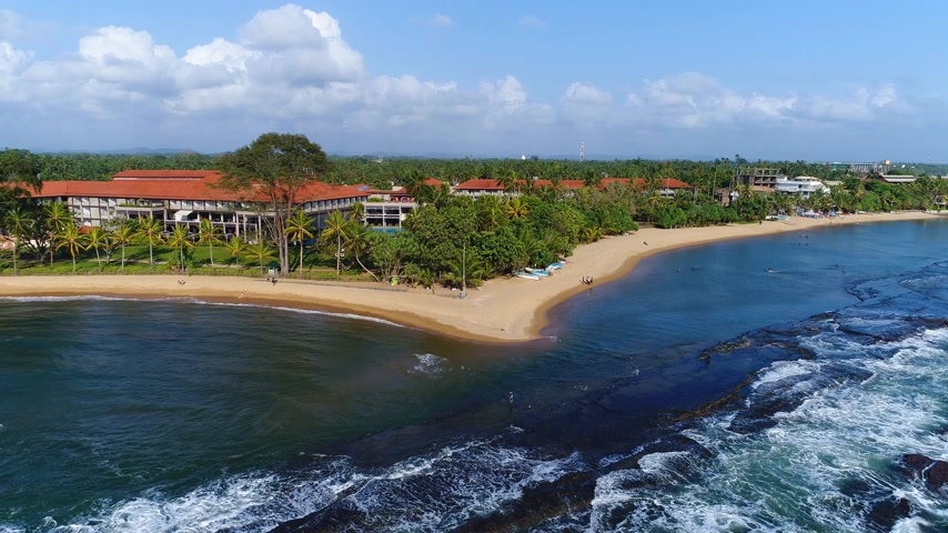 Aerival view in motion of the hotel near the sandy beach and light waves at the resort in Sri Lanka