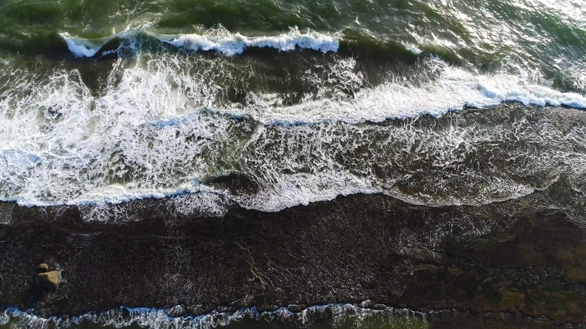 Aerial view from the top of sea waves that break down on the rocky ledge in the sea in Sri Lanka