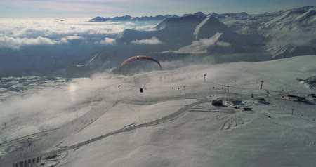 Amazing aerial video of paraplane at snow mountains. Close-up drone of paraglide winters mountains