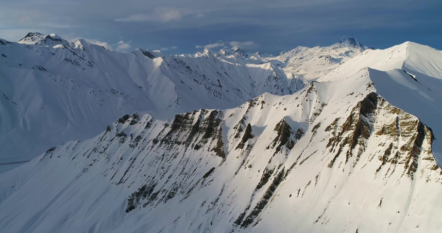 Imazing aerial shot of snowy mountain slope in Georgian mountains. Slowmotion drone video