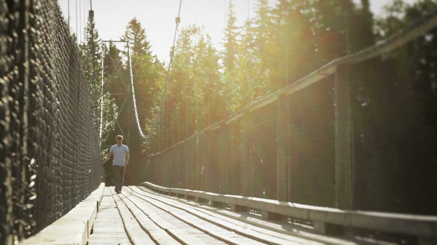 wooden path : Young Adult Walking on a Hanging Bridge