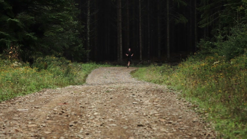 sprintel : Man Running Lonely on a Gravel Road in Forest