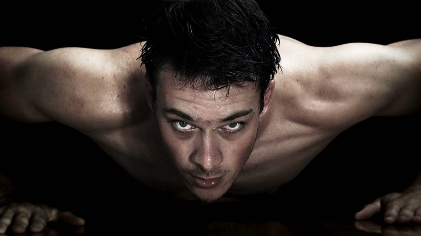 Zoom-in of a Man doing Push-ups isolated on a black Background
