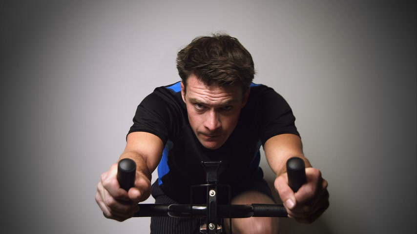 aerobik : 4K Motivated Young Man Sprinting and Sweating on a Stationary Bike with great Determination