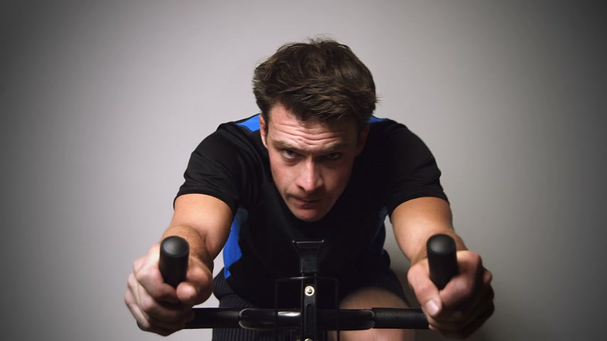 atleta : Motivated Young Man Sprinting and Sweating on a Stationary Bike with great Determination with Zoom-in Effect Stock Footage