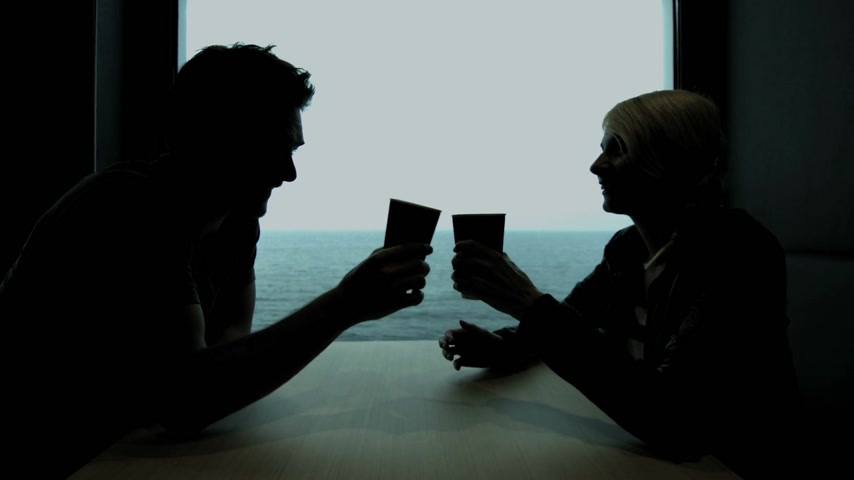 silhueta : Young Couple in Silhouette Enjoying a Coffee and Talking on a Boat Table Restaurant with the Ocean in Background