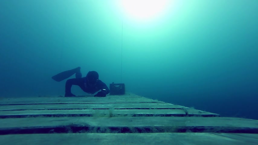 dengeleme : Freediving is fun ! Freediver crawling Underwater on a Wood Platform Stok Video