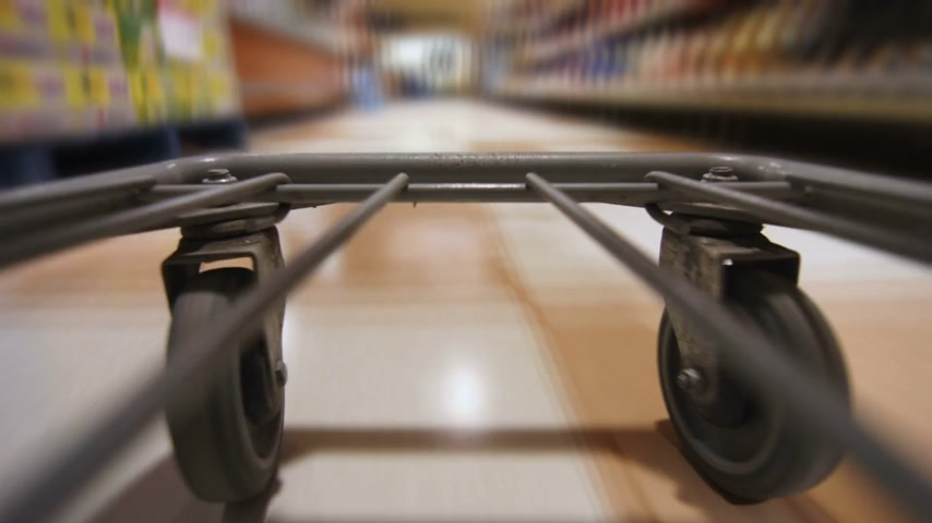 Detail of the Wheels of a Grocery Store Cart Moving inside the Super Market