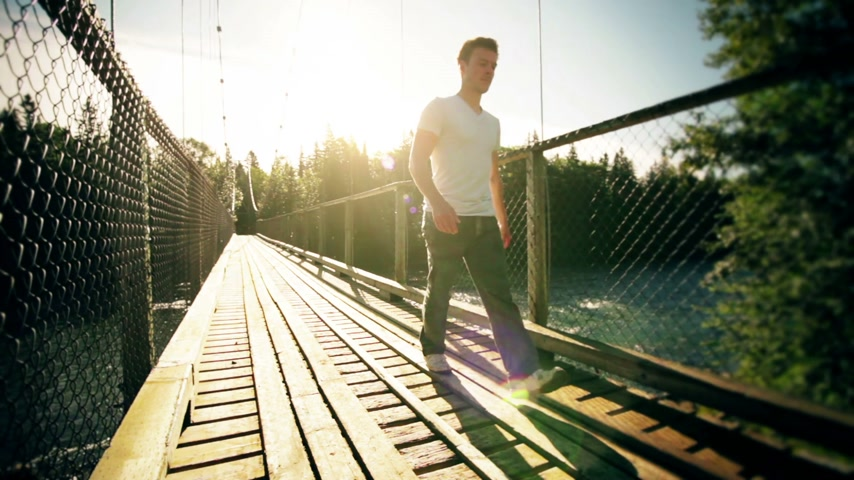 the suspension bridge : Motion-Photo Cinemagraph of a Young Man Crossing a Solid Hanging Bridge over a Flowing Water River