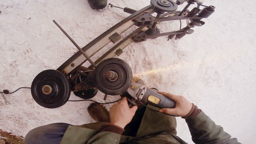 Man using a Grinder on a Metal Snowmobile Frame Outside