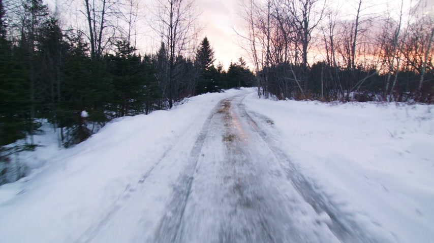 Suction Cut View from a Car Driving on a Small Off Road Path during a Winter Sunset